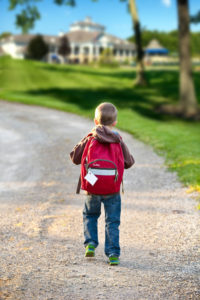 child wearing red backpack walking down the street in Barrington Estates