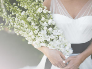 bride holding large bouquet of white flowers