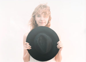 woman holding black hat
