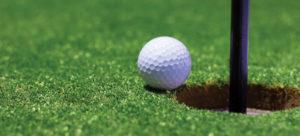 white golf ball next to hole