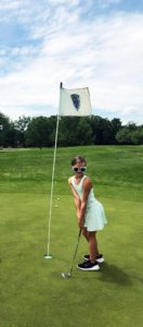 young girl next to hole on golf course