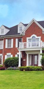 brick home with white balcony in Barrington Estates
