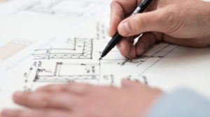 hands drawing blueprint plans